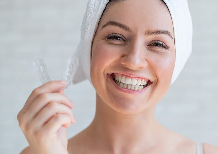SD Woman smiling and holding Oral Appliance