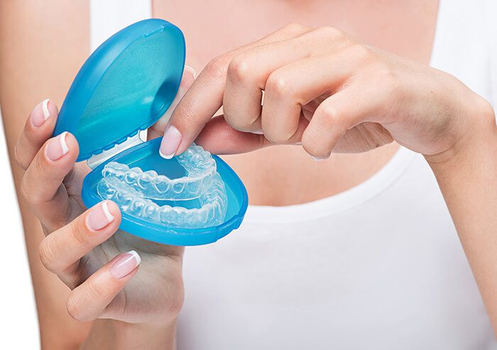 SD Woman taking out oral appliance from case