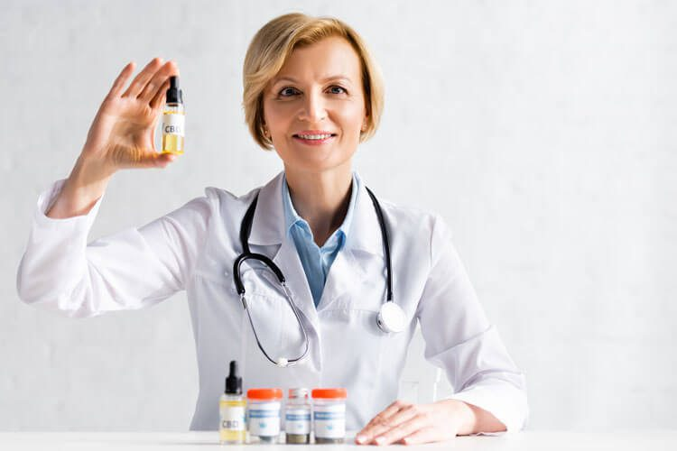 HF -Cheerful and mature doctor in white coat holding bottle with cbd