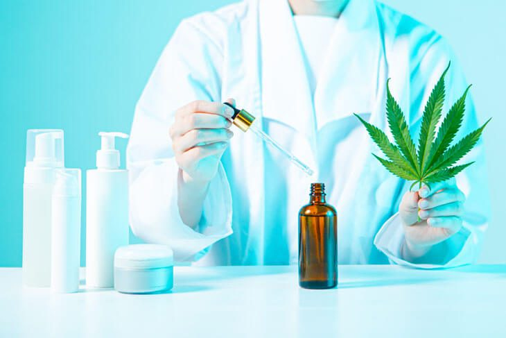 Doctor holding hemp leaf, testing CBD oil by pipette in blue laboratory light