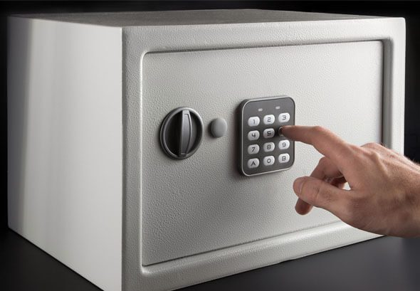 ALS -Hand opens a combination lock on the safe, a light safe on a dark background