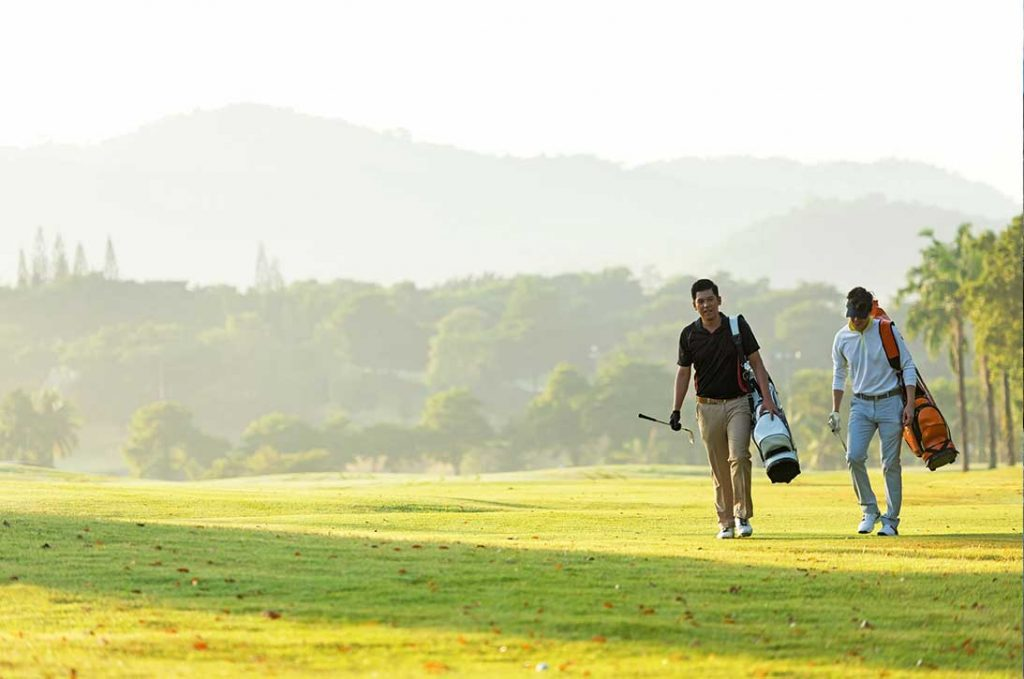 Group golf professional Golfer asian man walking in fairway with bag golf at golf club. Hobby in holiday and vacation with friends. Lifestyle and Sport Concept